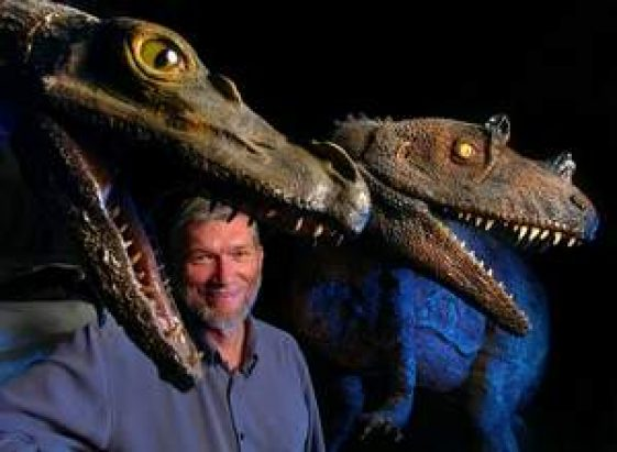 Ken Ham poses with dinosaur models in his unfinished $25 million Answers in Genesis museum.