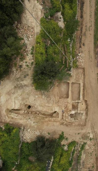 The aerial view of the Suba Cave excavation, showing cave entry and steps (middle-bottom right), exterior pools (middle right) and exterior corridor (middle center to left). The hillside rises to the left.
