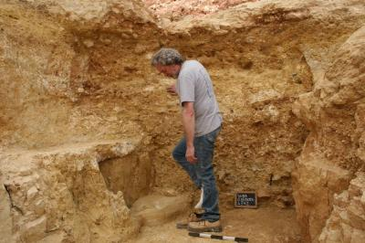 UNC Charlotte archaeologist James Tabor standing in the partially excavated corridor at the cliff face. Framing him above is what appears to be an archway filled with dirt.